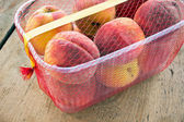 Fresh peaches in plastic bowl on wooden background — Stock Photo