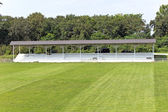 Wooden grandstand with roof and football field — Stock Photo