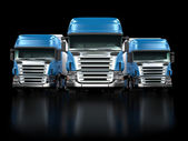 Heavy blue trucks isolated on black — Stock Photo