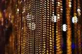 Bokeh cadena de oro con fondo negro y lámparas — Foto de Stock