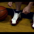 Young basketball player male ties his shoes laces  — Stock Video
