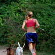 Woman is jogging with two dogs - Zdjęcie stockowe