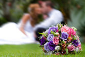 Wedding bouquet with bride and groom on background — Stock Photo