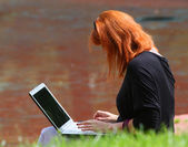 Donna testarossa con portatile — Foto Stock