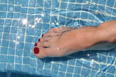 Woman beauty foot in the swimming pool — Stock Photo