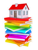 A small house on a stack of colorful books — Stock Photo