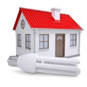 Energy saving lamp on the background of a small house — Stock Photo