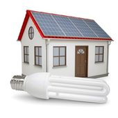 Energy saving lamp on the background of the house with solar panels — Stock Photo