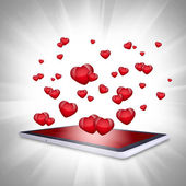 Red hearts fly out of the tablet PC — Stock Photo