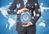 Man in suit holding alarm clock in hand — Photo