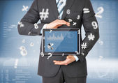 Businessman in a suit holding a tablet computer — Stock Photo