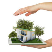 Hands holding tablet pc and small house with land — Stock Photo