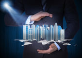 Man in suit holding skyscrapers in the hand — Stock Photo