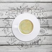 Cup of coffee with business sketches — Stock Photo