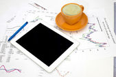 Tablet pc, cup of coffee and paper with graphs — Stock Photo