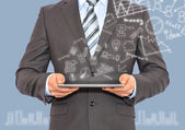 Man with tablet in hands and business sketches — Stock Photo