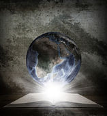 Over an open book is planet earth — Stock Photo