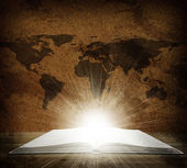 Over an open book is a map of the earth — Stock Photo