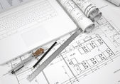 Scrolls architectural drawings and laptop — Stock Photo