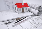 Scrolls architectural drawings and small house — Stock Photo
