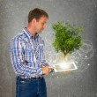 Man hold tablet pc with green tree — Stock Photo #50428401