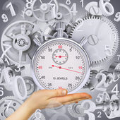 Hand hold stopwatch with figures and gears — Foto de Stock