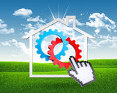 House icon with gears and computer hand — Stockfoto