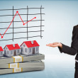 Businesswoman points hand on houses and money — Stock Photo