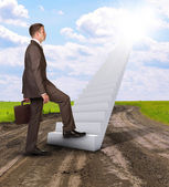 Businessman climbing up stairs leading to sky — Stock Photo