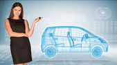 Businesswoman with key and wire frame car — Stock Photo