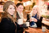Jóvenes bebiendo ponche en el mercado de navidad — Foto de Stock