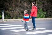 Moeder en zoon oversteken van de straat — Stockfoto