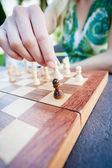 Woman moves piece in chess — Stock Photo