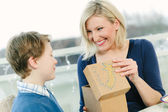 Mother receiving gift from her son — Stock Photo