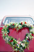 Bouquet on a red wedding car — Stock Photo