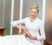 Foot massage by a therapist — Stock Photo