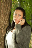 Young woman in the park talking on the cell phone — Stock Photo