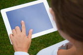 Woman holding and pointing at tablet PC — Stock Photo