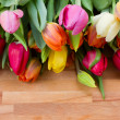 图库照片: Tulips on wooden table