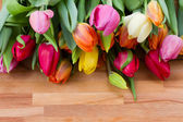 Tulips on wooden table — Stock Photo