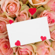 Greeting card with hearts on roses — Stock Photo