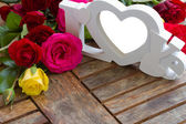 Love sign with roses on wooden table — Stock Photo