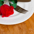 Knife and fork on plate  with rose — Stock Photo