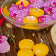 Bowl with orchids and candle on wooden table — Stock Photo