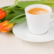 Stock Photo: Cup of coffee with orange tulips