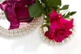 Pink rose with pearl necklace — Stock Photo