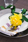 Table serving with narcissus flower — Stock Photo