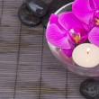 Orchids with candle and massage stones — Stock Photo