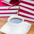 Photo: Cup of black coffee on table with books