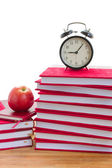 Alarm clock and books on a table — Stock Photo